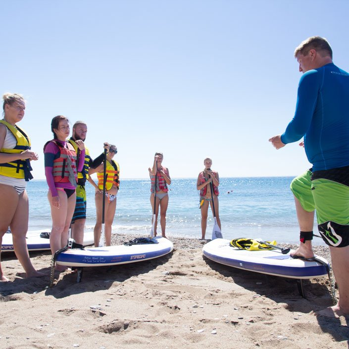Group of People following a SUP lesson on the beach