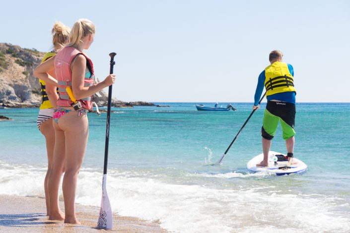 2 girls watching instructor demonstrate stand up paddling technique during sup lesson in Rhodes