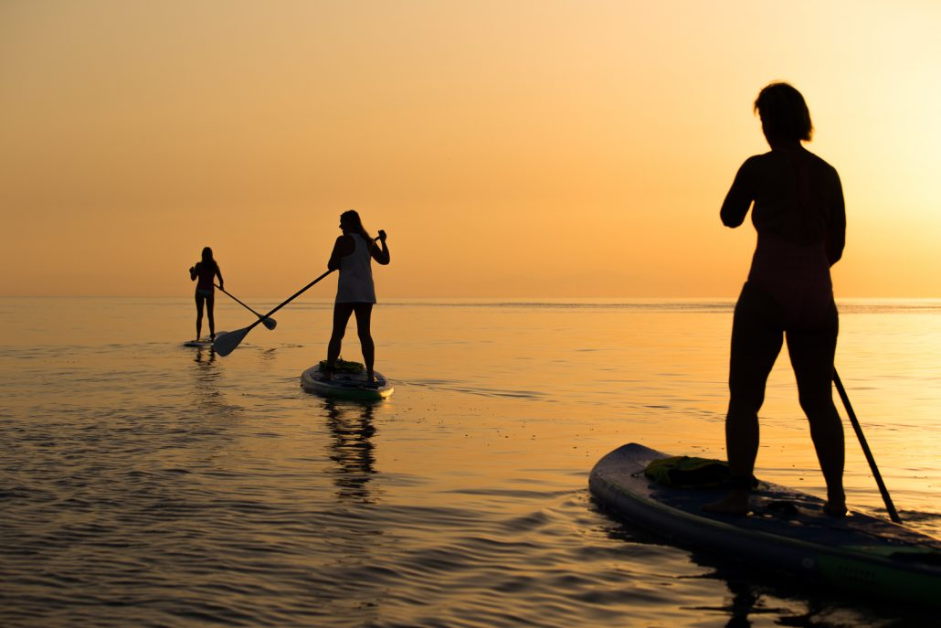 Silhouettes of stand up paddlers at the Sunrise Paddle tour on Rhodes