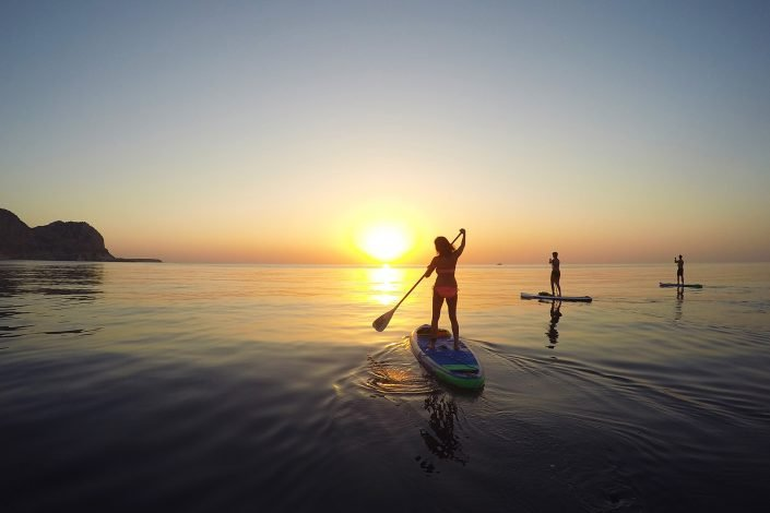 Stand Up Paddler paddling towards the sun on calm water in Rhodes as part of the Sunrise Paddle Tour