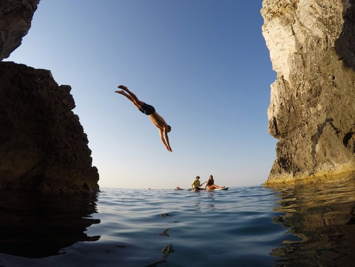 Person diving off cliff as part of a SUP Adventure