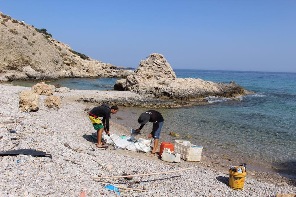 2 people are collecting rubbish from a beach near Stegna, Rhodes