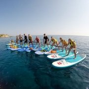 Group of stand up paddlers in line, trying to step over on to each other's board