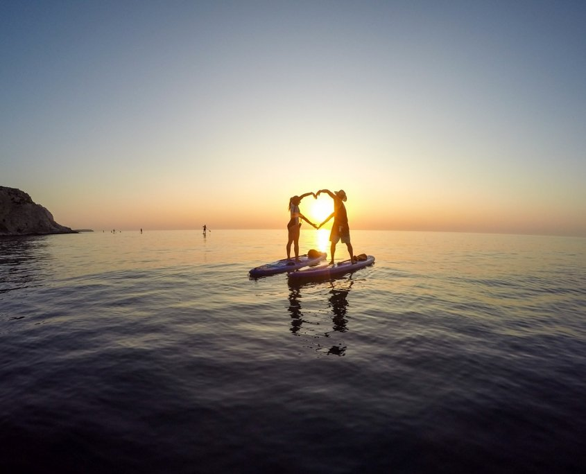 2 people creating a heart shape in front of the rising sun while standing on stand up paddle boards