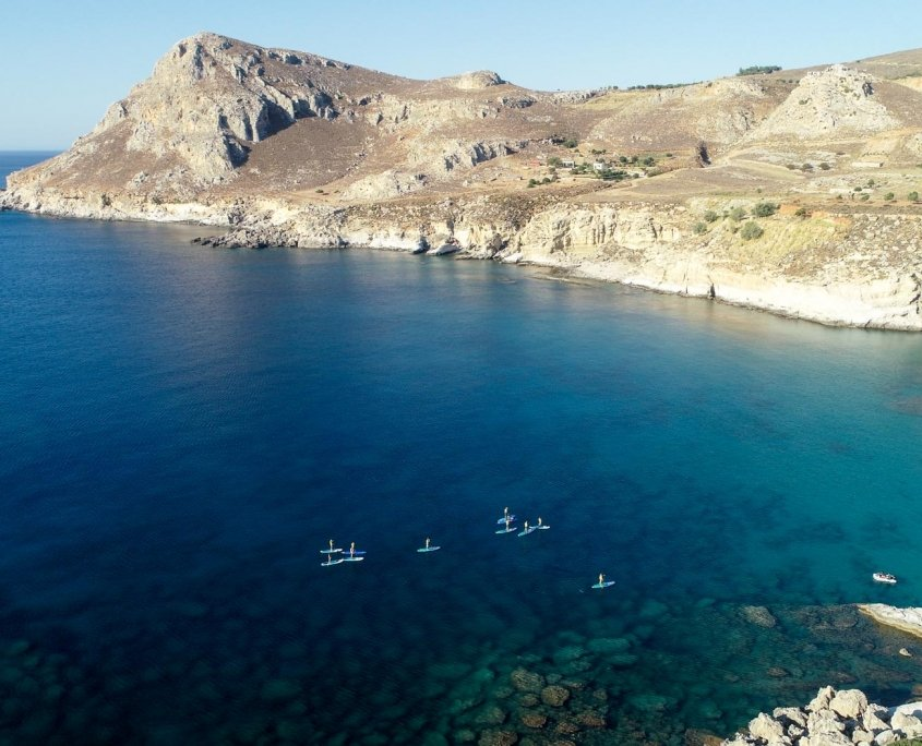 Drone view of people stand up paddling in bay with clear blue water and surrounded by rocky terrain and cliffs.