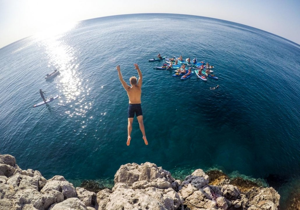 Guy jumps of cliffs into blue sea in front of a group of paddlers