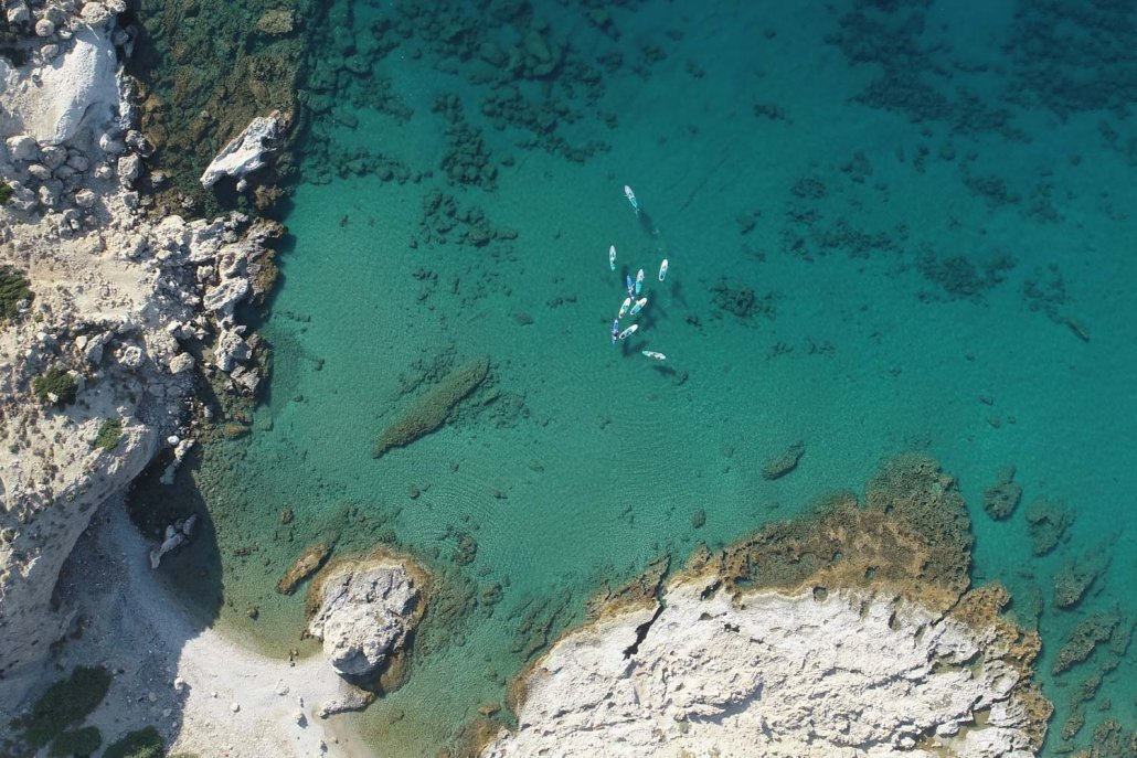 Drone view of group of paddlers on clear blue water