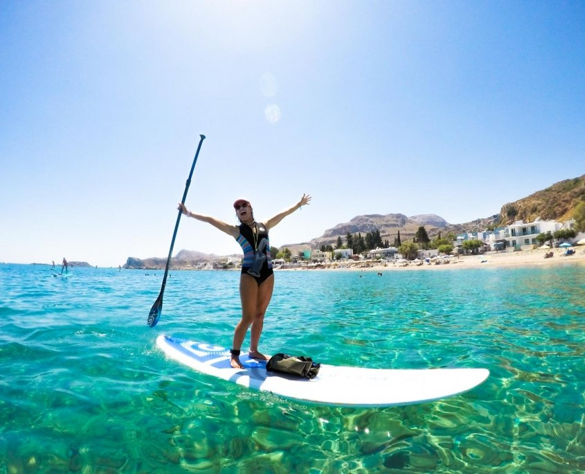 Girl on SUP cheering with paddle in the air