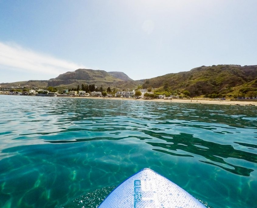 First person view of paddle board, clear blue water and beach